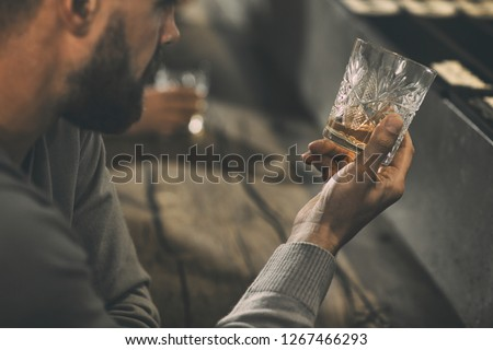 Close up of man's hand holding crystal glass of whiskey or brandy. Bearded man drinking and tasting strong drinks and elite alcohol in bar. Concept of expensive alcoholic beverages. #1267466293