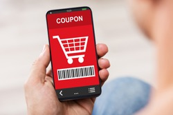 Close-up Of Man's Hand Holding Mobile Phone With Shopping Coupon