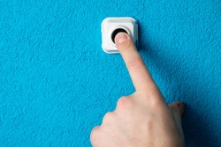 Close-up of man's hand pressing the button of doorbell on blue wall