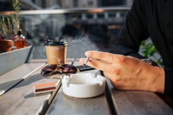 Close up of man's hands hold cigarette in hand. He has it above white plate. There are glasses and cup of drink on talbe. It is sunny outside.