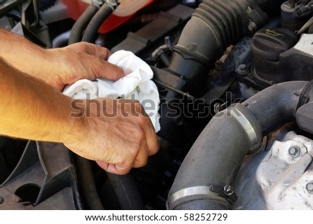 close-up of man's hands holding a piece of cloth checking the engine of a car