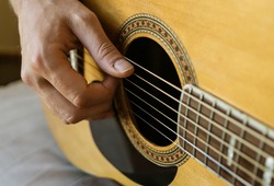 Close up of man's hands playing acoustic guitar. Hobby passion concept.