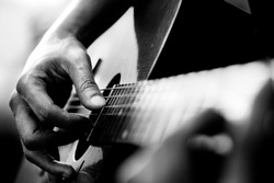 Close up of man's hands playing acoustic guitar. Musical instrument for recreation or hobby passion concept.