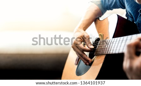 Close up of man's hands playing acoustic guitar. Musical instrument for recreation or hobby passion concept. ストックフォト ©