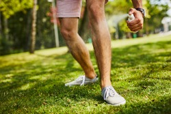 Close-up of man's legs being sprayed with insect repellent in the park outdoors