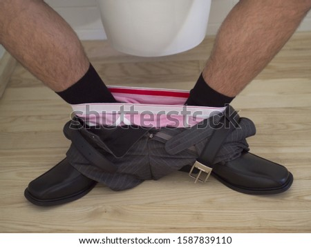 Close up of man's pants around ankles in bathroom