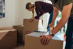Close up of man sealing a packing box with adhesive tape while a woman placing articles in another box. Couple packing their items for moving into a new house.
