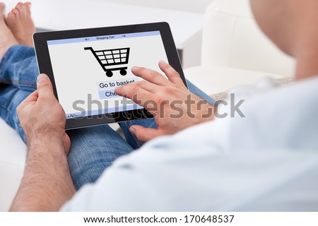 Close-up Of Man Shopping Online With Digital Tablet