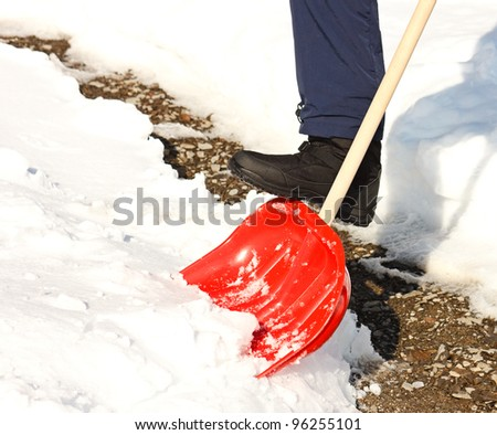 Close-up of man shoveling snow with red shovel.Cleaned path in background.