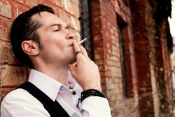 Close-up of man smoking cigarette while leaning on a brick wall.