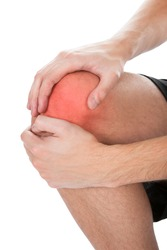 Close-up Of Man Suffering From Knee Injury On White Background