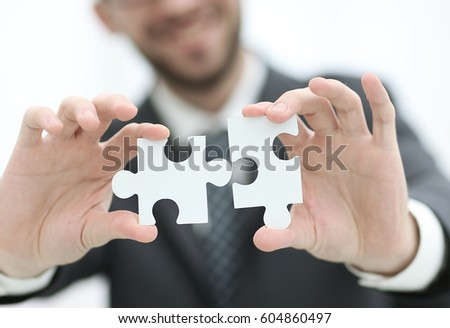 Close up of man trying to connect puzzle pieces. Stock photo ©