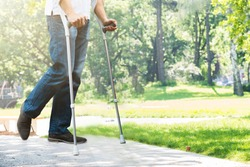 Close-up Of Man Walking With Crutches In Park