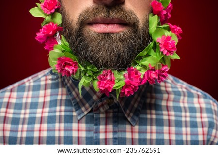 Close-up of man with flowers in his beard is standing against red background.