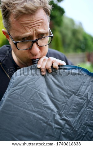 Close up of man with glasses blowing up a self inflatable sleeping pad for camping                               ストックフォト ©