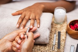 Close up of manicurist hands clipping client nails in a luxury spa. Young woman getting manicure treatment with hands kept on towel. Clipping nails, hand care and nailcare at beauty salon.