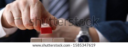 Close-up of mans hand putting red unique brick on top of light wooden blocks. Metaphor to management and authority. Leadership ideas and uniqueness concept