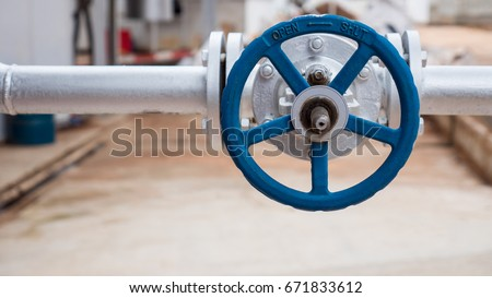 Close up of manual operate blue metal ball valve and pipes industrial equipment at factory.