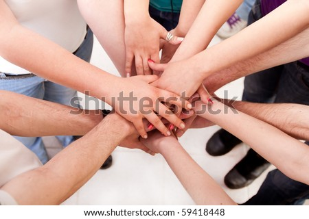 close up of many hands in circle - students connection