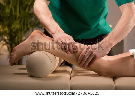 Close-up of masseur\'s hands kneading female calf