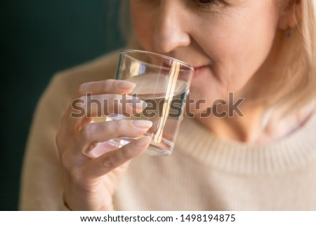 Close up of mature old lady hold glass drinking pure mineral still filtered water for body balance, elderly woman take care of health enjoy clean aqua recommend dieting, healthy lifestyle concept