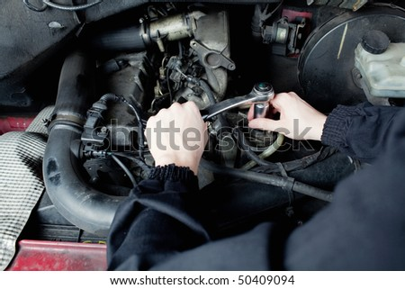 Close-up of mechanic repairing an engine