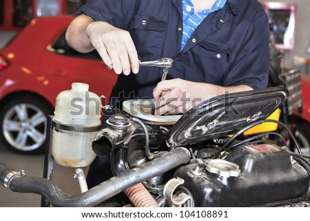 Close-up of mechanic repairing an engine in garage.