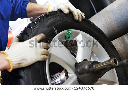 Close-up of mechanic repairman hands during balancing automobile car wheel on balancer