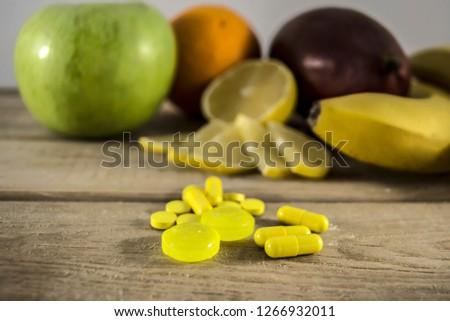 Close up of medical pills, lemon, banana, apple, and orange. Vitamines for health. Vitamine C, supplements for healthy life. Natural alternative to antibiotics.