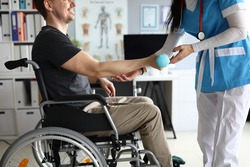 Close-up of medical worker helping to develop arm lifting blue dumbbell. Nurse in uniform working with disabled person. Man in wheelchair in clinic. Medicine and physical therapist concept