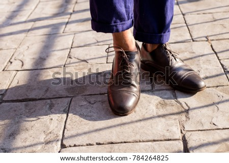 Close up of men food wearing genuine leather Brogue shoes or vintage leather Brogue shoes on the concrete road
