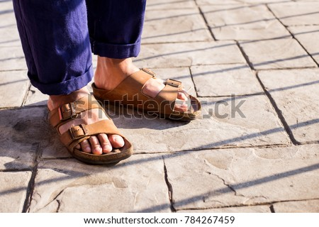 Photo of  Close up of men food wearing genuine Sandal leather shoes or vintage leather sandal shoe on the concrete road