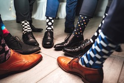 Close up of men legs wearing formal shoes and funny colorful socks. Seven friends feet in circle composition.