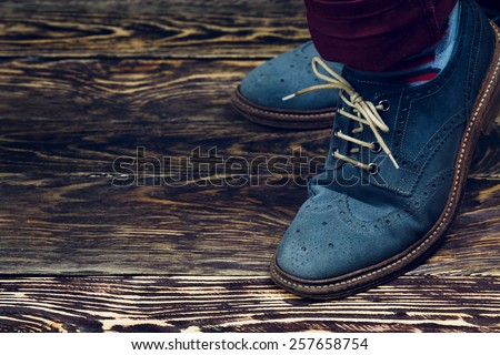 Close up of men\'s brogues (also known as derbies,gibsons or wingtips) made from blue oiled suede