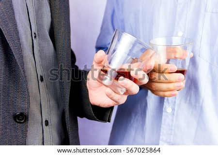 Close-up of men's  hands cheering up with glasses of whisky - Shutterstock ID 567025864