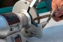 Close-up of men's hands sharpening scissors on an electric sharpener. Repair of home tools with your own hands