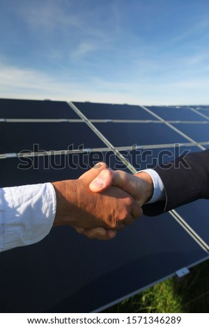 Close-up of men shaking hands at Photovoltaic power plant in Rott, Bayern, Germany