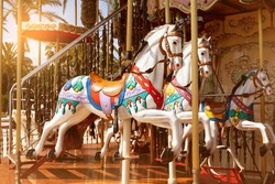 Close-up of merry go round carousel horses in sunset