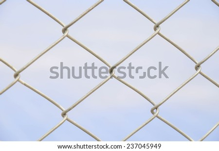 Close up of metal fence for barrier or boundary against blue sky background  #237045949