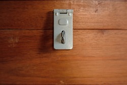 Close up of Metal Hasp staple on wooden box, Key Locking Devices to secure storage.