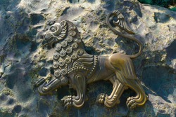Close-Up Of metal Lion Statue placed on a stone wall