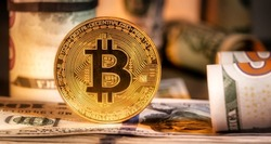 Close up of metal shiny bitcoin crypto currency coins on US dollar bills. Electronic decentralized money concept. Bitcoin is convenient payment in global economy market.