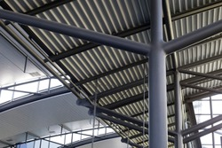 Close-up of metal structures of industrial building. Abstract modern architecture or construction industry image with steel pillars and girders supporting corrugated ceiling / roof.