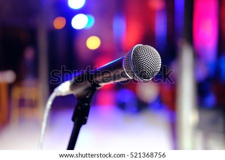 Close up of microphone in concert hall or conference room on colorful blurred background