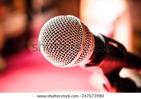 Close up of microphone in karaoke room or conference room / Microphone in karaoke room or conference room/ Close up of microphone in front of pink background (microphone, karaoke, music )