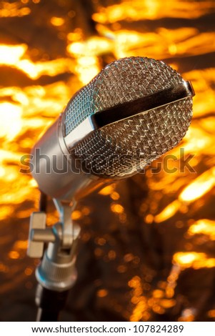 close up of microphone on the stand on golden background
