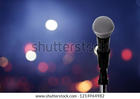 Close up of microphone setting on stand with colorful light bokeh background in conference hall .