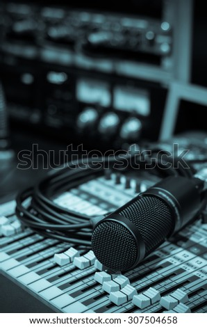 Close up of microphone with equipment on mixer in music studio, music instrument concept