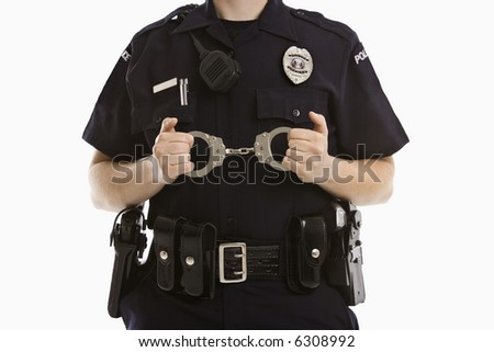Close up of mid adult Caucasian policewoman holding locked handcuffs.