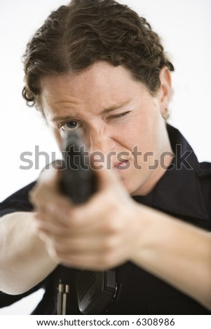 Close up of mid adult female Caucasian law enforcement officer aiming gun at viewer with one eye closed.
